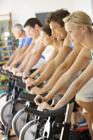 Men And Women Cycling In Spinning Class