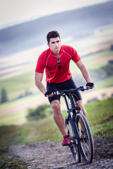Man Cycling Up A Hill
