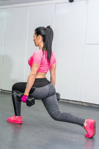Woman Doing Weighted Lunges At Home