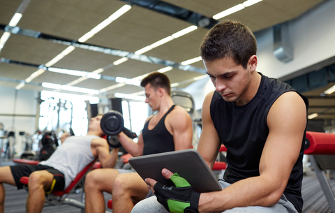 Man Recording Personal Bests On Tablet At The Gym