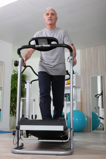 Middle Aged Man On Treadmill At Home