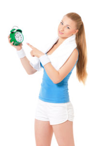 Fitness Woman Holding An Alarm Clock
