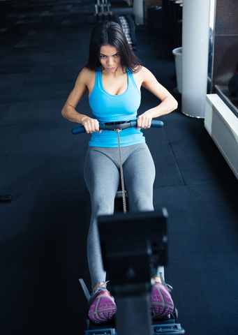 girl using rowing machine at home